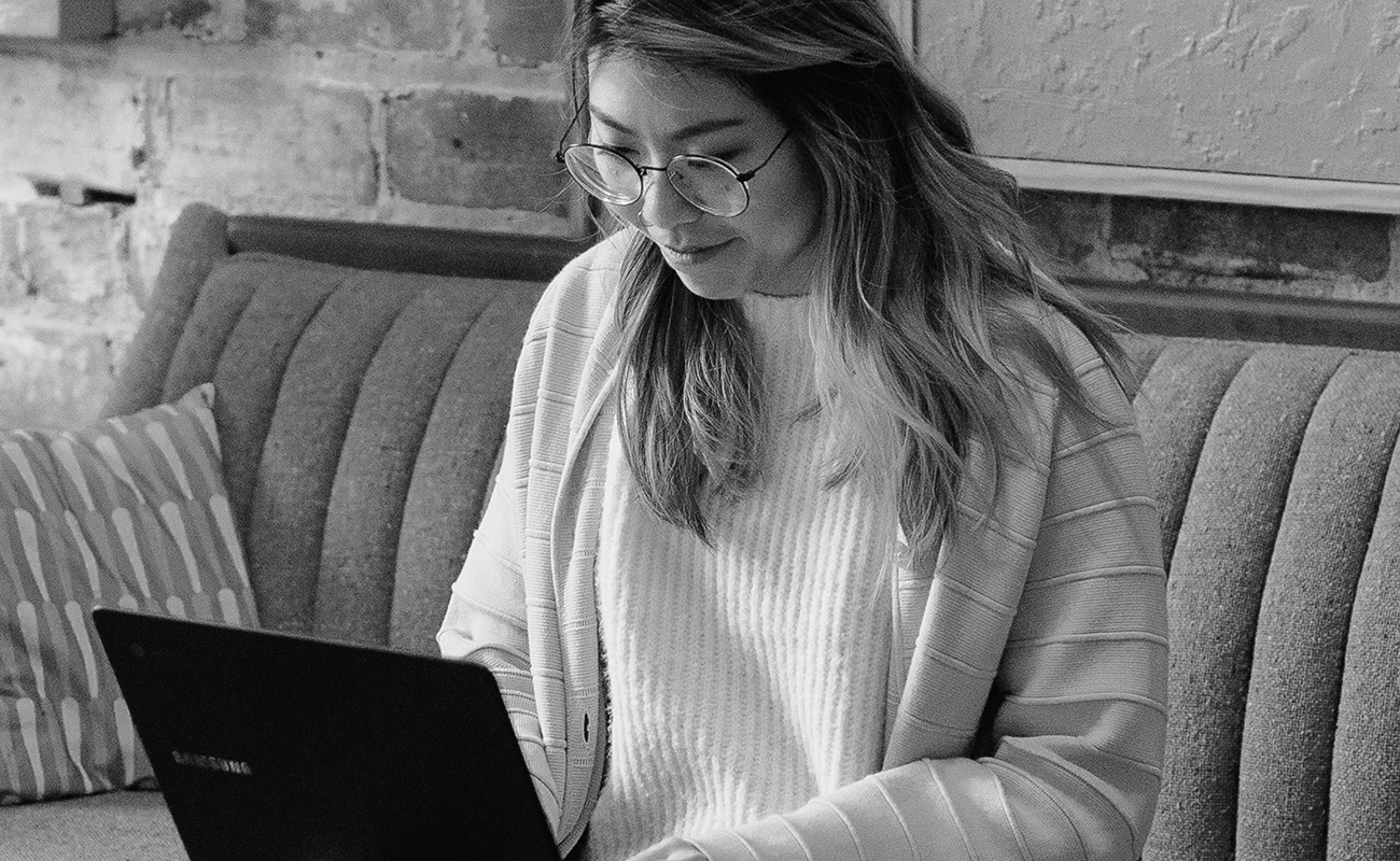 A black and white photo of an Asian woman with long hair wearing glasses and a light sweater under a cardigan is typing on her laptop while smiling.