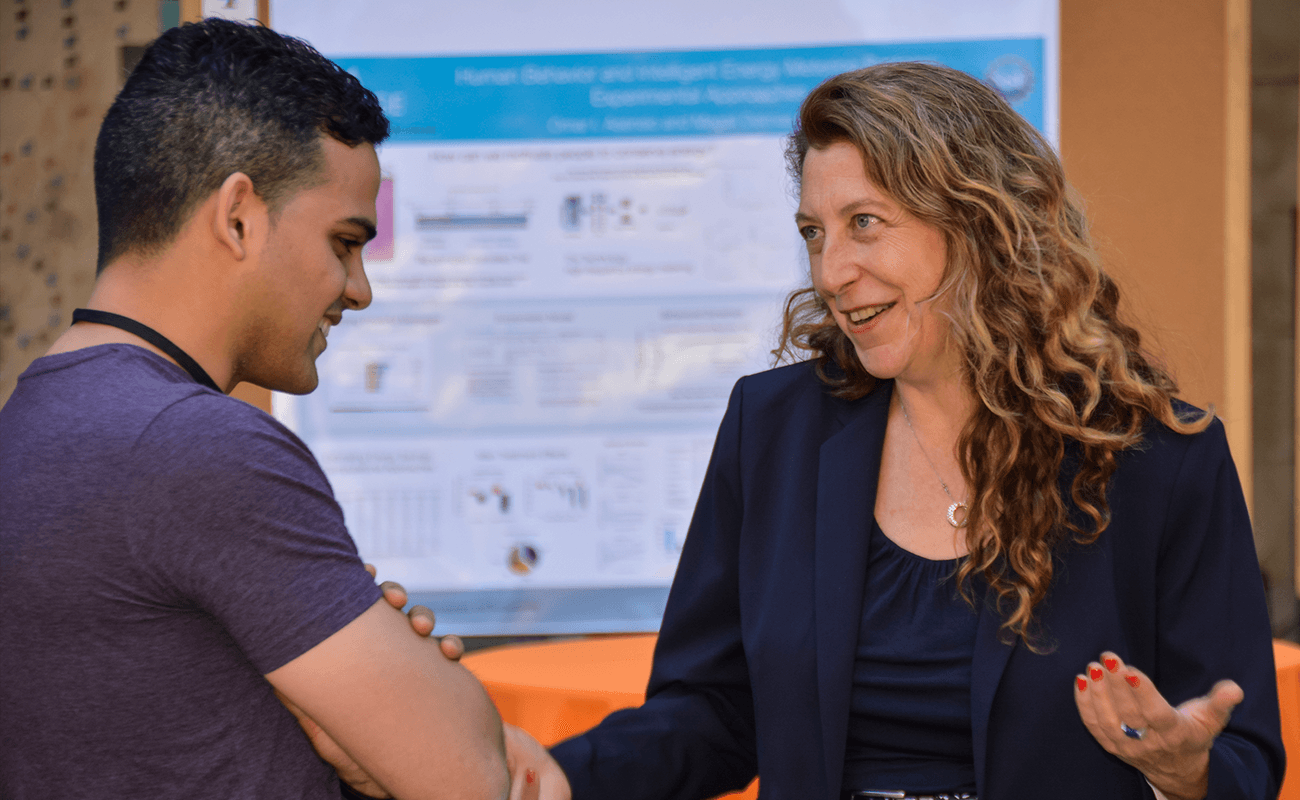 The photo shows two people talking (student and administrator) in front of a research poster.